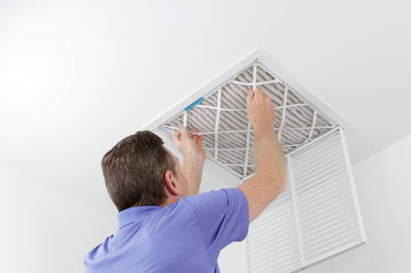 Caucasian male removing a square pleated dirty air filter with both hands from a ceiling air duct