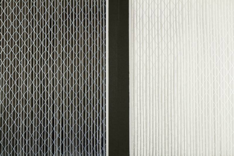 Close up side by side comparison of a dirty gray home air filter next to a clean white house furnace air filter