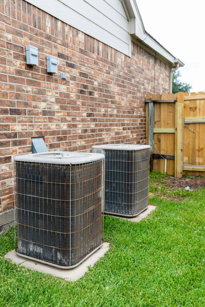 Older air conditioner units next to brick home with copy space