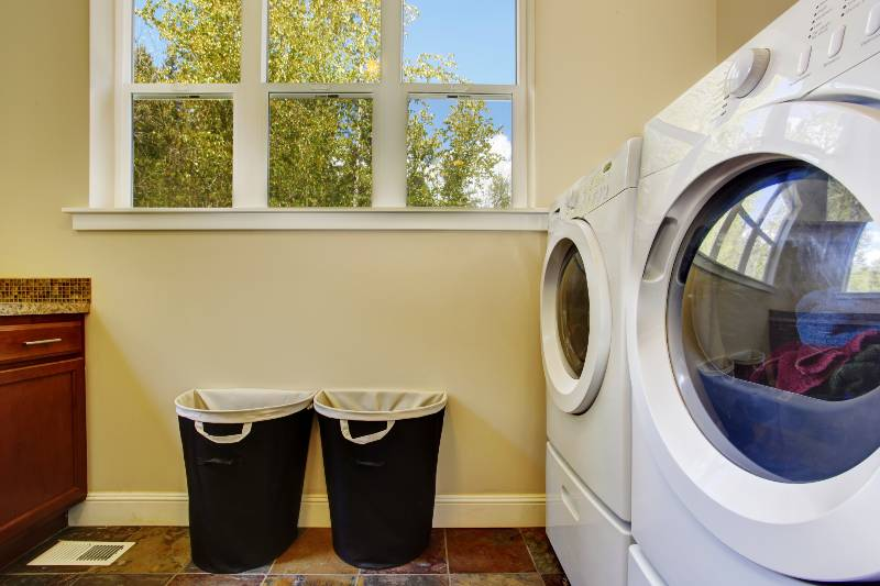 Bright ivory laundry room with white modern appliances and black baskets