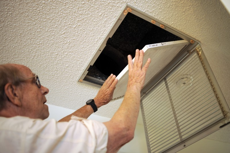 Older homeowner changes the filter in his ceiling airconditioner duct work